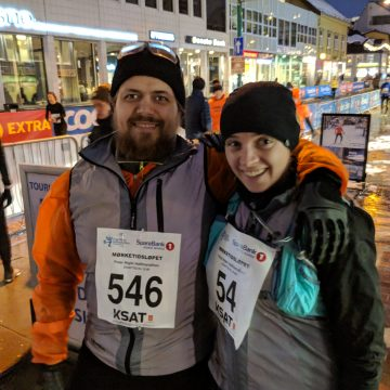 Two runners wearing winter clothes and race numbers