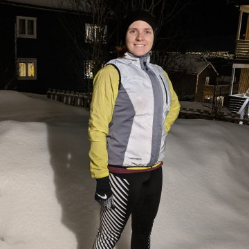 Girl standing outside in the snow wearing reflective running gear